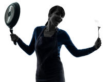 Woman happy cooking holding frying pan silhouette Stock Image
