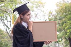 Woman happy graduate holding bord. In the garden stock photography