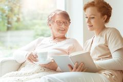 Woman and happy grandmother. Woman reading a book while sitting with happy grandmother drinking tea Stock Image