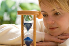 Woman with happy memories. Daydreaming by a hourglass - shallow DOF Stock Photo