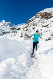 Woman happy running on snow in winter Stock Photo