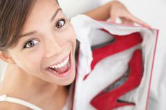 Woman happy for shoes as gift. Woman getting shoes as gift. Young beautiful woman surprised and happy to receive red high heels shoes as a present Stock Photos