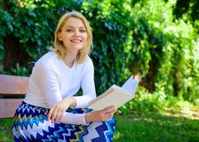 Woman happy smiling blonde take break relaxing in garden reading book. Girl sit bench relaxing with book, green nature. Background. Lady enjoy self imrovement stock photo
