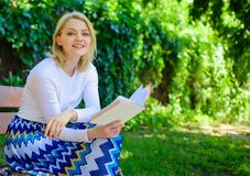 Woman happy smiling blonde take break relaxing in garden reading poetry. Girl sit bench relaxing with book, green nature. Background. Lady enjoy poetry in royalty free stock photography