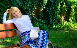 Woman happy smiling blonde take break relaxing in garden reading poetry. Lady enjoy poetry in garden. Enjoy rhyme. Girl. Sit bench relaxing with book, green royalty free stock photo