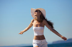 Woman happy smiling joyful on beach. Happiness bliss freedom concept. Woman happy smiling joyful with arms up dancing on beach in summer during holidays travel Stock Photos