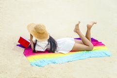 Woman happy smiling and read books on the beach on a beautiful . royalty free stock photography