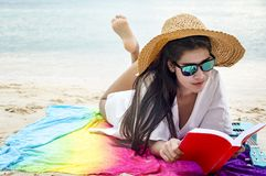 Woman happy smiling and read books on the beach on a beautiful . stock photo