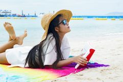 Woman happy smiling and read books on the beach on a beautiful . royalty free stock image