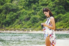 Woman happy smiling and take a camera on the beach on a beautiful . Pretty girl asian in casual looking away and smile , laughing. royalty free stock photography