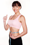 Woman Happy With Successful Weightloss. Smiling young woman giving a thumbs up sign while measuring her waist to show she is happy with her weightloss Stock Photography