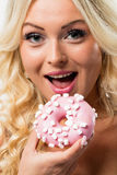Woman happy to eat a pink donut Royalty Free Stock Images