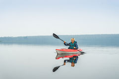Woman happy to paddle from red kayak on calm lake Stock Images
