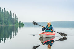 Woman happy to paddle from red kayak on calm lake Stock Photography