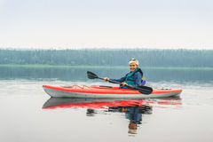 Woman happy to paddle from red kayak on calm lake Stock Photos