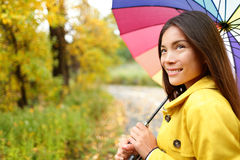 Woman happy with umbrella under the rain. During Autumn forest walk. Girl enjoying rainy fall day looking away smiling. Mixed race Caucasian / Asian chinese Stock Photography