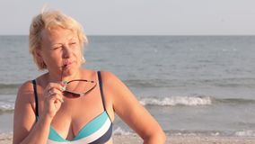 Woman happy on vacation taking off glasses and sunbathing on the beach. stock video