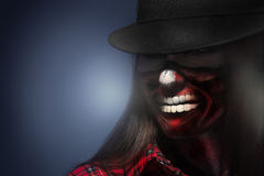 Woman in har with scary face art for halloween night looking awa Royalty Free Stock Photo