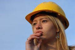 Woman in a hard hat. Young female architect apprentice with yellow hard hat stock photo