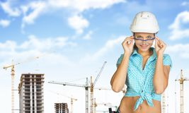 Woman in hard hat adjusting protective glasses Royalty Free Stock Image