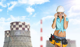 Woman in hard hat adjusting protective glasses Stock Photos