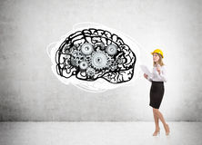 Woman in hard hat and brain with cogs Royalty Free Stock Image