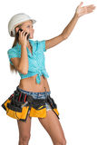 Woman in hard hat calling on mobile phone and Royalty Free Stock Image