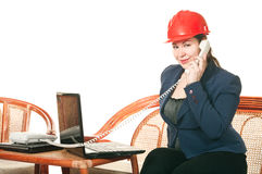 Woman in hard hat calling by phone Stock Photography