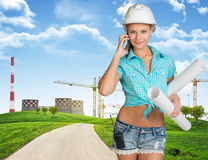 Woman in hard hat, holding drawing rolls calling Royalty Free Stock Images