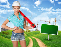 Woman in hard hat, holding large spirit level Stock Photography