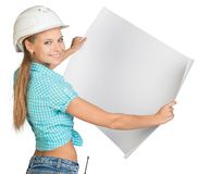 Woman in hard hat showing blank sheet of drawing Royalty Free Stock Images