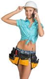 Woman in hard hat and tool belt calling on mobile Royalty Free Stock Photos