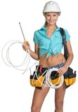 Woman in hard hat and tool belt holding coil of Stock Image