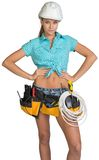 Woman in hard hat and tool belt posing Royalty Free Stock Photography