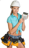 Woman in hard hat and tool belt showing calculator Royalty Free Stock Photo