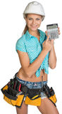 Woman in hard hat and tool belt showing calculator Royalty Free Stock Photos