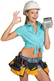 Woman in hard hat and tool belt showing calculator Stock Photo