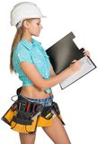 Woman in hard hat and tool belt writing on blank Stock Images