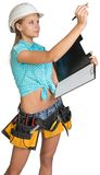 Woman in hard hat and tool belt writing on blank Stock Photo