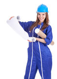 Woman in hardhat and coveralls reading blueprints Royalty Free Stock Photography