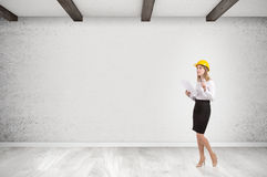 Woman in hardhat in empty room Stock Image
