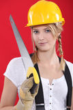 Woman with a hardhat and handsaw stock image
