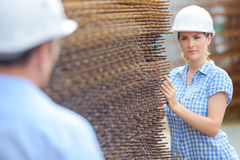 Woman in hardhat next to stack metal Stock Photo