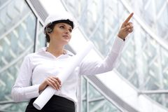 Woman in hardhat pointing finger stock photo