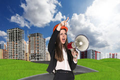 Woman in hardhat screaming in megaphone Stock Photo