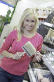 Woman in hardware store. Woman holding item in hardware store stock photography