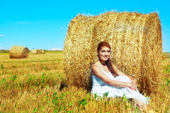 Woman in the harvested  wheat field Stock Photos