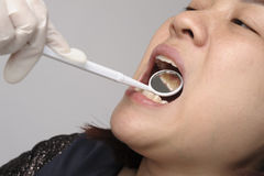 Woman has checking toot and mouth. By dental mirror Royalty Free Stock Images