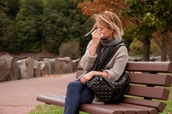 Woman has cold or flu.  Allergy. Woman has cold or flu. Cough. Girl sitting on bench in the park Royalty Free Stock Photo