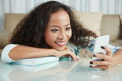 Woman has a conversation on cellphone. Smiling pretty woman sitting at the table with book and has a conversation online using her mobile phone stock photos